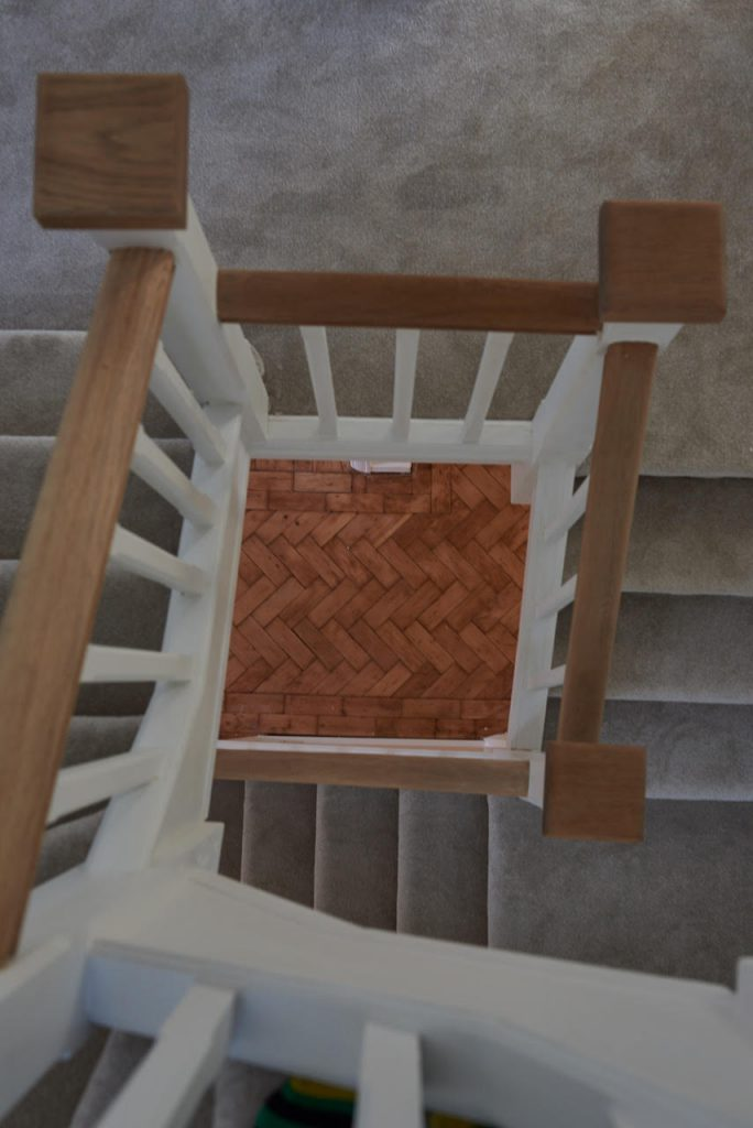Looking down staircase to parquet flooring